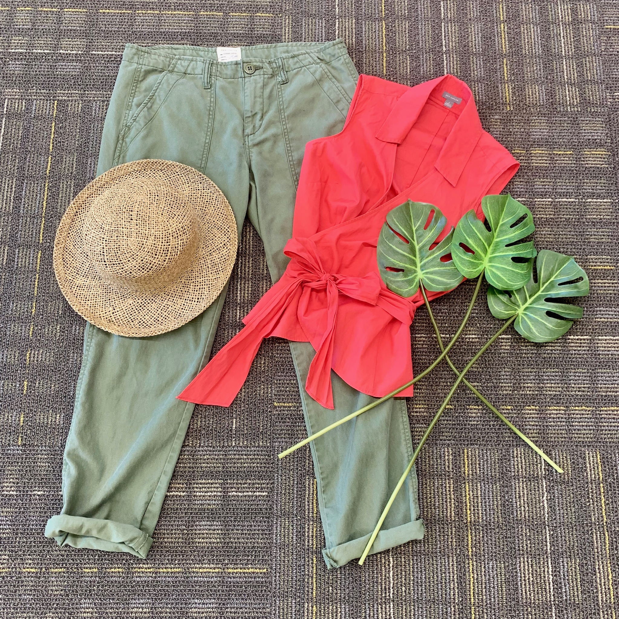 Green pants with coral wrap sleeveless blouse and straw hat